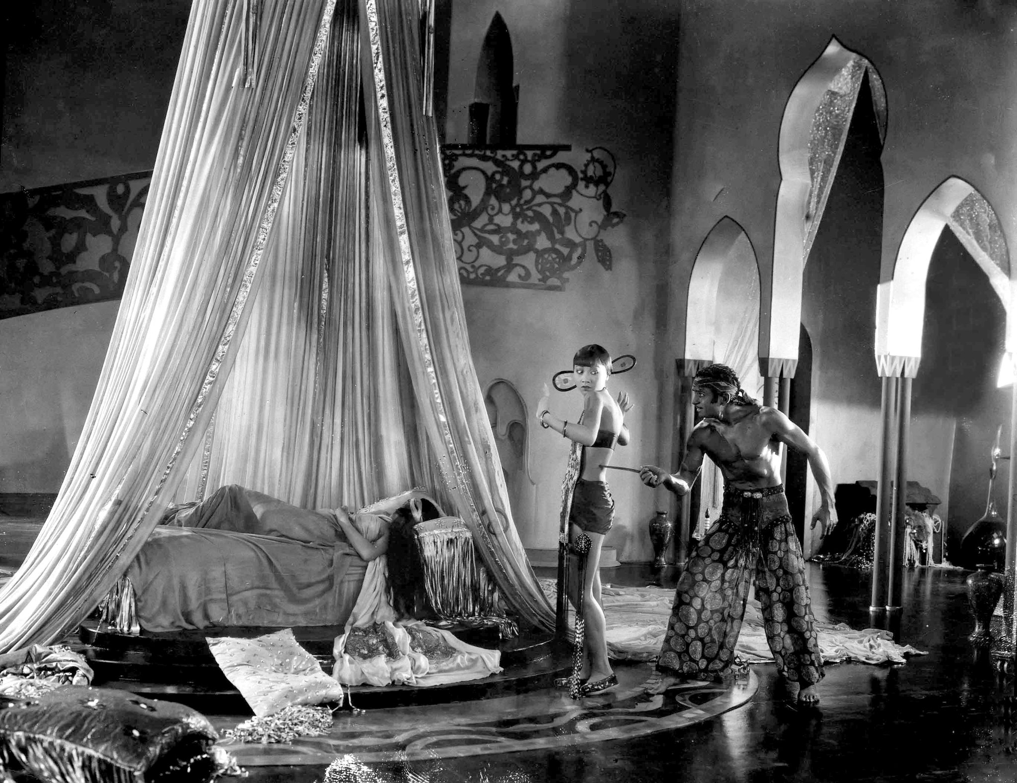 Douglas Fairbanks as Ahmed, the Thief of Bagdad threatening Anna May Wong as the Mongol Slave with Julanne Johnston as The Princess sleeping 1924 The Thief of Bagdad picture image