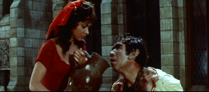 Esmeralda (Gina Lollobrigida) gives Quasimodo (Anthony Quinn) a drink, 1956 Hunchback of Notre Dame picture image